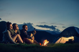 Three friends camping with fire on mountain at sunset - 107918266