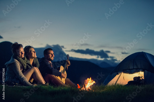 Three friends camping with fire on mountain at sunset Poster