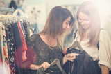 Two smiling friends enjoy in clothing shop - 107920059