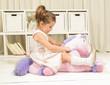 Obrazy na płótnie, fototapety, zdjęcia, fotoobrazy drukowane : Cute little girl riding on a pink pony toy. Children imagination or creativity concept. Princess and Fairy tale unicorn