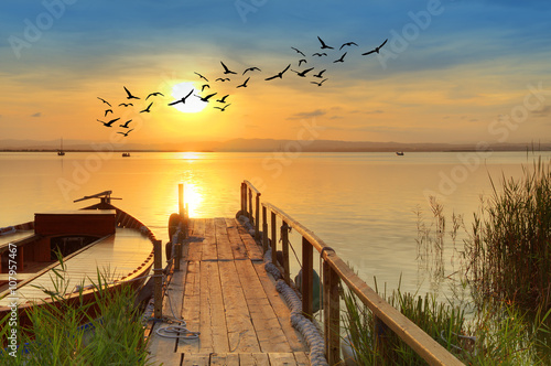 puesta de sol sobre un embardero tradicional de madera