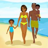 african american family walking happy along beach