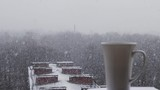 Hot coffee being poured into the cup outside the window with snow fall, trees and snow covered roofs.