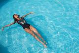 Красивая девушка в купальнике загарает в бассейне