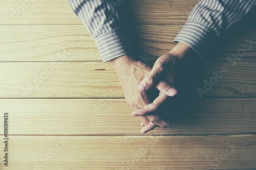 Poster Close up on male hands folded in prayer at a wooden table