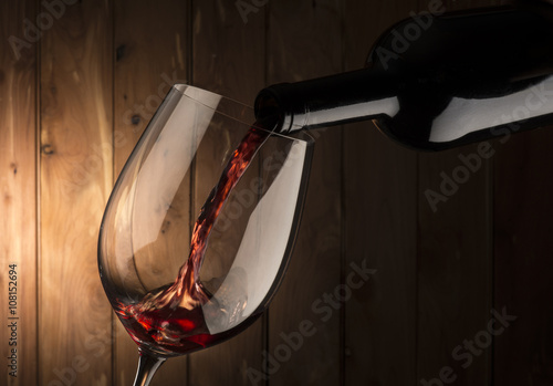 glass with red wine on wooden background Poster