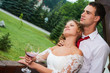Wedding couple celebreting their big day with red wine at the hotel veranda