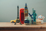 Fototapety Travel and tourism concept with souvenirs from around the world. Planning summer vacation, money budget trip concept. Saving money for vacation.