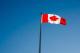 Canadian flag waving over blue sky