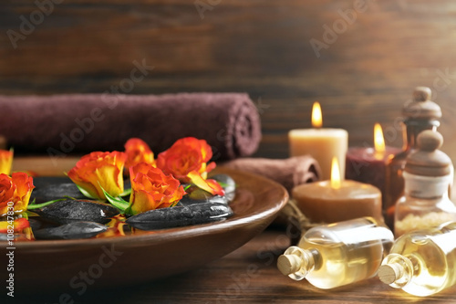 Spa wooden bowl with water, flowers and stones on wooden background © Africa Studio
