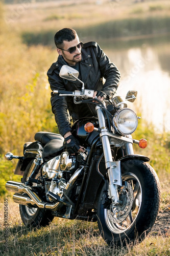 young brutal man in a black jacket and glasses standing near a motorcycle Slika na platnu