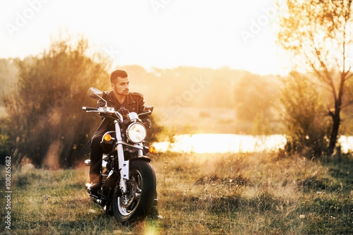 Poster young brutal man in a black jacket and glasses sits near a motorcycle