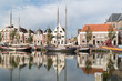 Old houses on quay of Zuiderhaven harbor canal with boats in Harlingen, Friesland, Netherlands