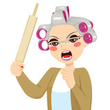 Senior woman angry holding roll pin with aggressive expression screaming