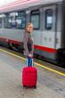 Leinwandbild Motiv Frau wartet auf Zug auf Bahnhof