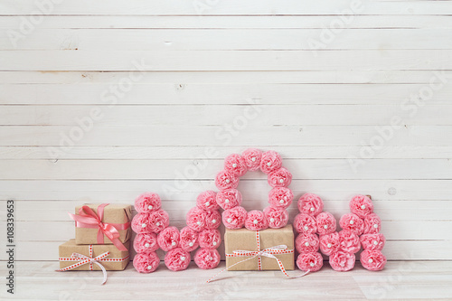 Mothers day message of pink paper flowers over white wooden boar