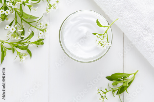 Natural cosmetic cream with herbal flowers skincare product in glass jar on white background
