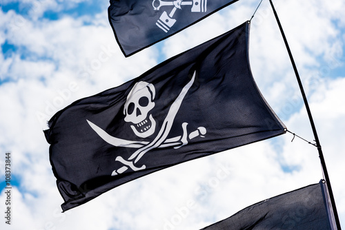 Poster Pirate flags in the wind on a blue sky flags in the wind on a blue sky