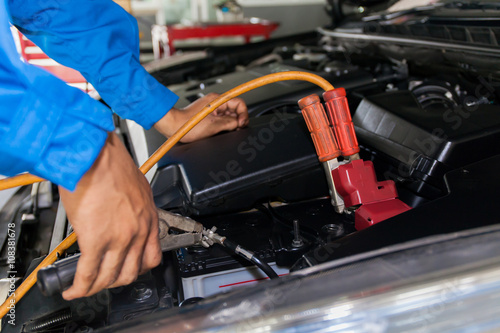 Poster Mechanic attaching jumper cables with battery car - closeup