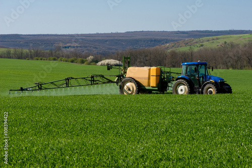 Aluminium Trekker Tractor spraying pesticide in a field of wheat