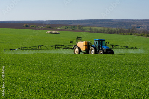Poster Tractor spraying pesticide in a field of wheat