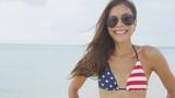 Happy American suntan girl smiling on US beach travel holiday wearing aviator sunglasses and USA flag bikini fashion swimwear. Stars and stripes pattern united states style.