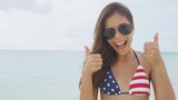 Cheering woman joyful doing fun thumbs up with US flag bikini on american beach vacation. Happy Asian girl celebrating USA stars and stripes pattern beachwear. Excited sexy model portrait smiling.