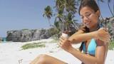 Sunscreen woman applying suntan lotion on bikini body. Beautiful smiling happy asian woman with suntan cream in bottle lying on beach during summer travel vacation. Multiracial female model