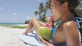 Happy beach fun bikini girl relaxing drinking healthy fresh coconut water on tropical suntan holiday on a Caribbean island. Woman enjoying the sun on summer vacation lying down on sand.
