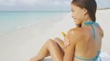 Beach bikini woman applying sunscreen lotion on body and shoulders. Asian multiracial girl model putting suntan oil spray for tan holding plastic bottle lying on beach on summer travel vacation.