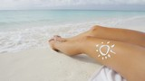 Sexy bikini body sunbathing on beach vacation with drawing of sun in sunscreen lotion on tanned skin woman relaxing lying down on sand in sunny tropical summer vacation. Slim body weight loss closeup.
