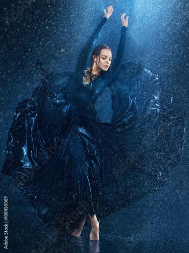 Fototapeta The young beautiful modern dancer dancing under water drops