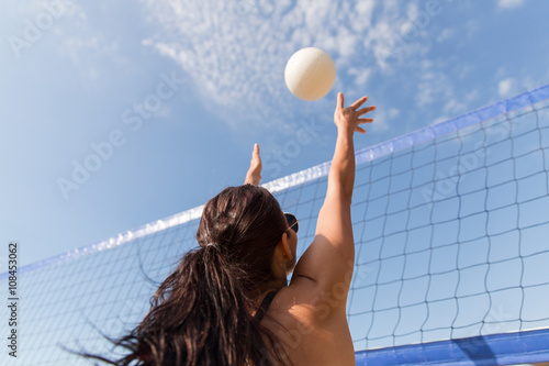 Poster young woman with ball playing volleyball on beach