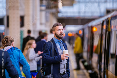 Zdjęcia Hipster businessman with coffee cup at the train station