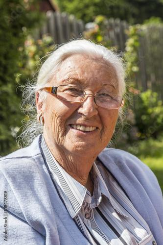 Femme âgée assise dans son jardin Poster