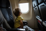 Fototapety Little boy looking out of window in airplane