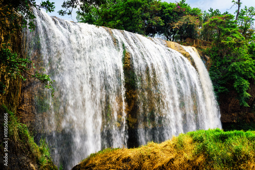 Plakat Scenic waterfall with crystal clear water among green woods