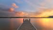 Strandurlaub, langer Steg führt ins Wasser zum Sonnenuntergang