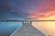 pastellfarbener Sonnenuntergang am Meer mit Holzsteg