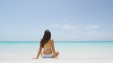 Vacation travel bikini woman on Caribbean beach. Young Lady with slim sexy body sitting on tropical white sand beach in Caribbean looking at perfect turquoise ocean. Luxury destination. SLOW MOTION.