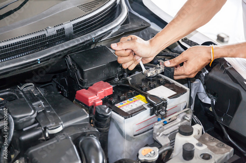 Poster Mechanic engineer fixing car battery in garage (selective focus)