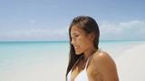 Gorgeous brunette lying on the beach sunbathing on sunny blue sky day