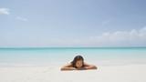 People beach lifestyle. Woman sunbathing relaxing suntanning on sea shore. Beautiful woman model in bikini is lying on idyllic beach. Attractive female is on her summer vacation.