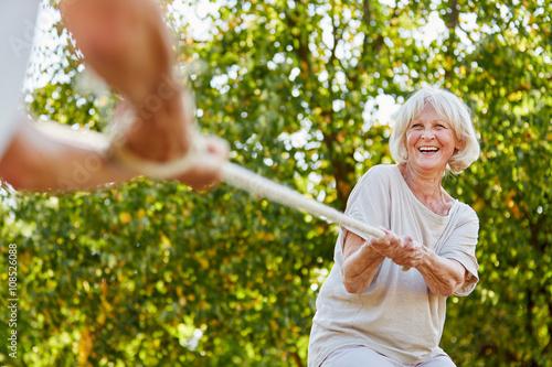 Fröhliche Seniorin beim Tauziehen Poster