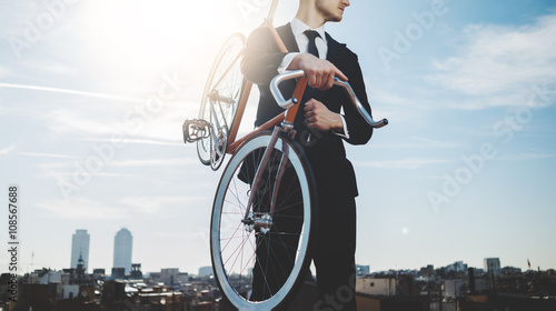 Professional businessman wearing black suit and standing with modern orange bicycle, panoramic view of the city in the backgound, flare light, outdoors