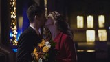 the pair on the background of night city. The groom embraces the bride at night. The lights of the big city