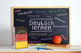 Blackboard in a German classroom with the message LEARN GERMAN and some text - 108625250