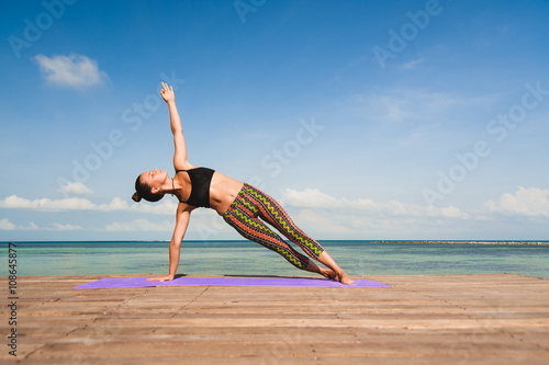Woman doing yoga in the morning at the sea плакат