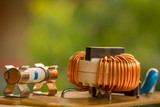 Electromagnetic coil, inductor. Small winding coils and fuses are mounted on a baseplate. Background.