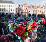 Bicycles decorated with flowers with blurred background of houses. Brugge, Belgium